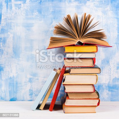 istock Stack of colorful hardback books, open book on blue background 502131066