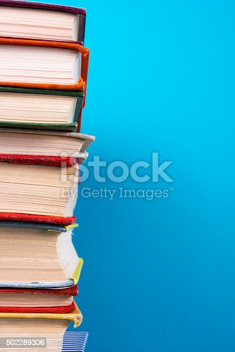 istock Stack of colorful hardback books, open book on blue background 502289306