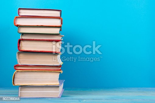 istock Stack of colorful hardback books, open book on blue background 502289344