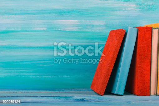 istock Stack of colorful hardback books, open book on blue background 502289424