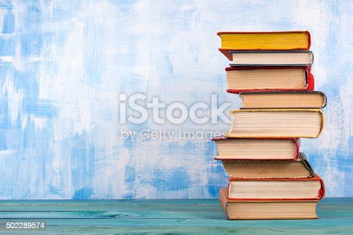istock Stack of colorful hardback books, open book on blue background 502289574