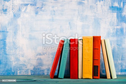 istock Stack of colorful hardback books, open book on blue background 502289596