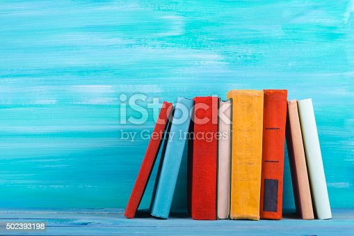 istock Stack of colorful hardback books, open book on blue background 502393198
