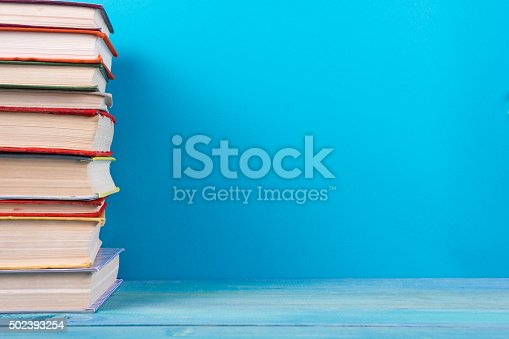 istock Stack of colorful hardback books, open book on blue background 502393254