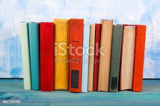 istock Stack of colorful hardback books, open book on blue background 502725150