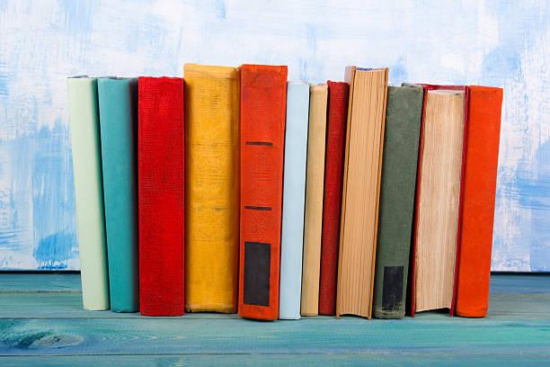 Pila de coloridas y de tapa dura libros, libro abierto en fondo azul - foto de stock