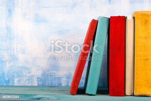 istock Stack of colorful hardback books, open book on blue background 502842334