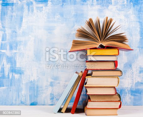 istock Stack of colorful hardback books, open book on blue background 502842350