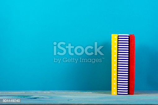 istock Stack of colorful hardback books, open book on blue background 504449240