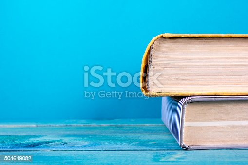 istock Stack of colorful hardback books, open book on blue background 504649082