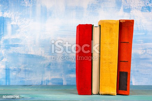 istock Stack of colorful hardback books, open book on blue background 504694296