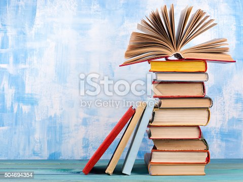 istock Stack of colorful hardback books, open book on blue background 504694354