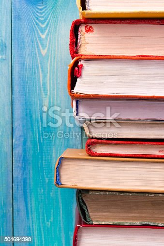 istock Stack of colorful hardback books, open book on blue background 504694398