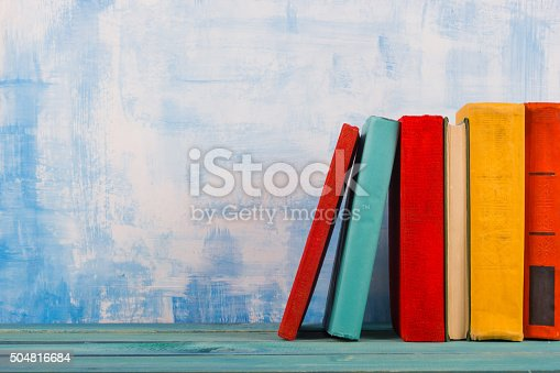 istock Stack of colorful hardback books, open book on blue background 504816684
