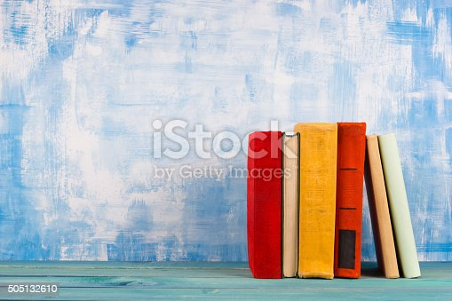 istock Stack of colorful hardback books, open book on blue background 505132610