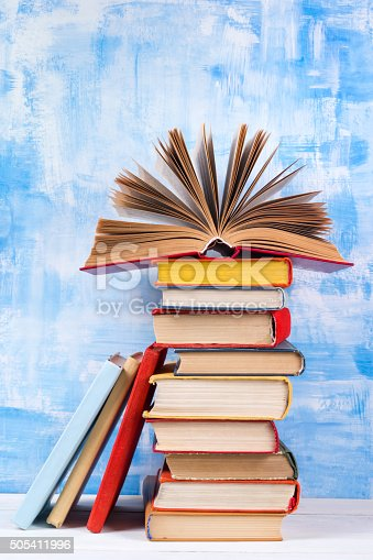 istock Stack of colorful hardback books, open book on blue background 505411996