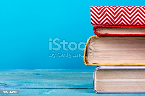 istock Stack of colorful hardback books, open book on blue background 505644810