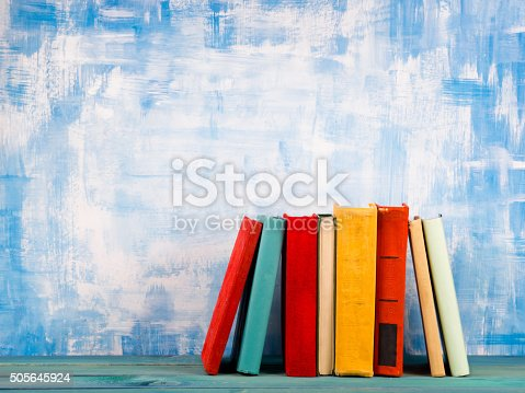 istock Stack of colorful hardback books, open book on blue background 505645924