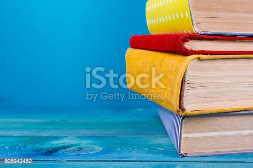istock Stack of colorful hardback books, open book on blue background 505943452