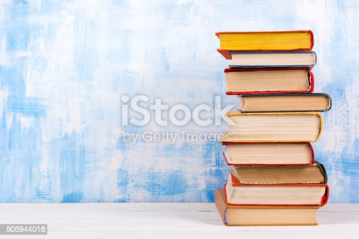 istock Stack of colorful hardback books, open book on blue background 505944018