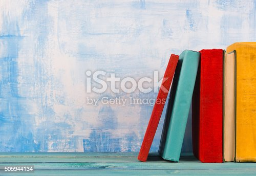 istock Stack of colorful hardback books, open book on blue background 505944134