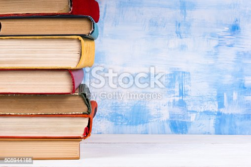 istock Stack of colorful hardback books, open book on blue background 505944168