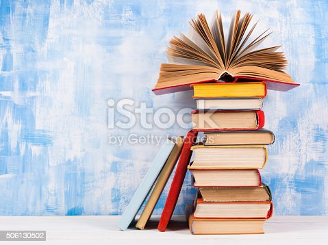 istock Stack of colorful hardback books, open book on blue background 506130502
