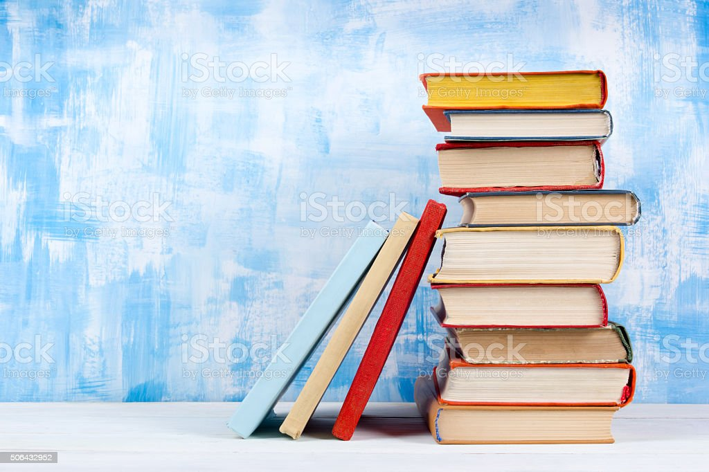 Stack of colorful hardback books, open book on blue background Stack of colorful hardback books, open book on blue background Abstract Stock Photo