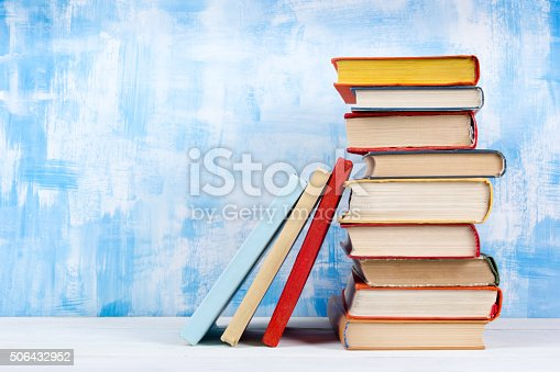 istock Stack of colorful hardback books, open book on blue background 506432952