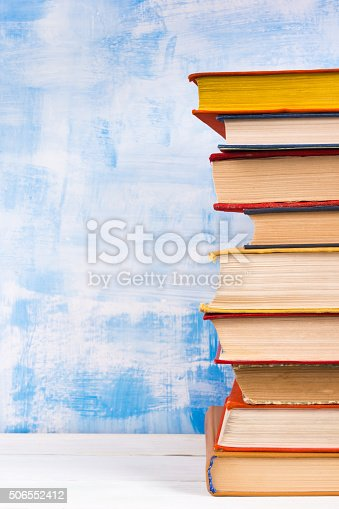 istock Stack of colorful hardback books, open book on blue background 506552412