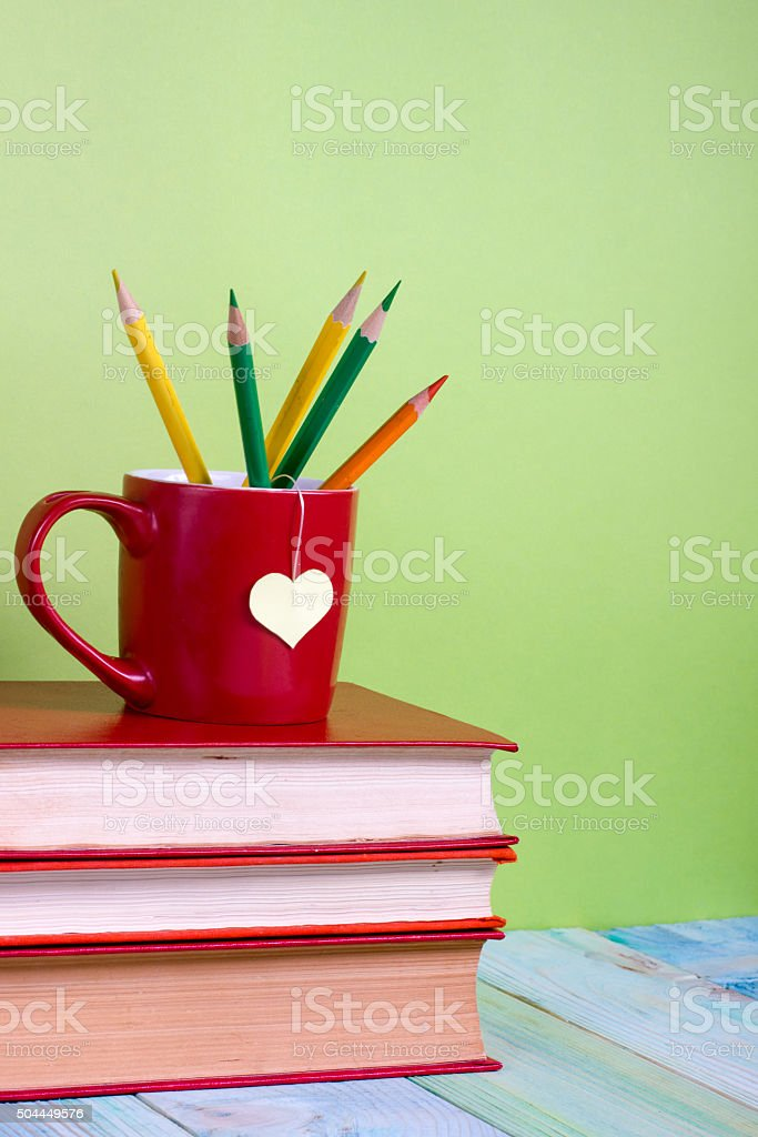 Stack of colorful hardback books, open book on green background stock photo