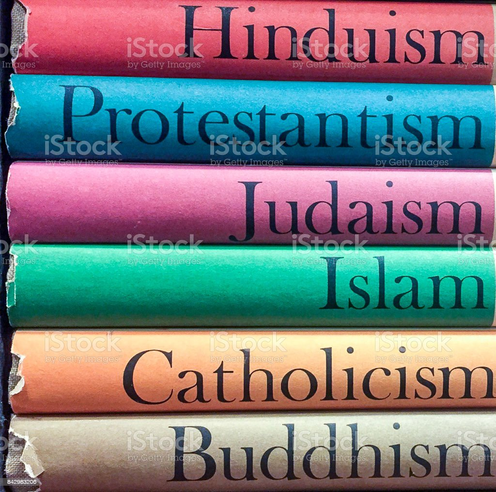 A Stack of Colorful Religious and Spiritual Books: Islam, Catholicism, Buddhism, Judaism, Protestantism, Hinduism stock photo
