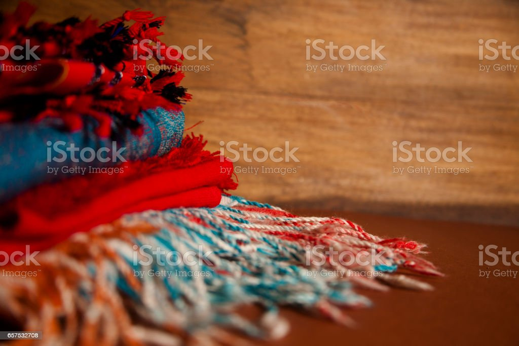 Stack of colorful scarves on wooden background. stock photo