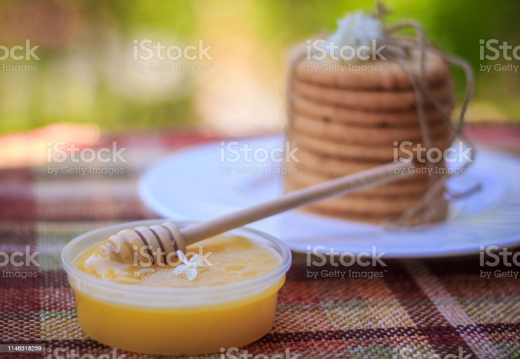 A stack of cookies, a plate of honey and flowers. Food and drink....