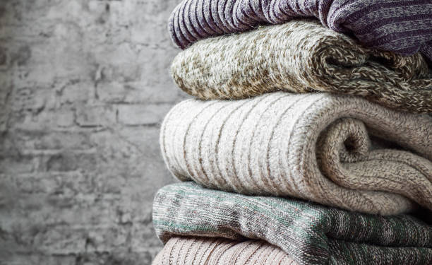 stack of cozy knitted sweaters on gray wall background - caxemira imagens e fotografias de stock