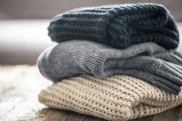 stack of cozy knitted sweaters - wool stock photos and pictures