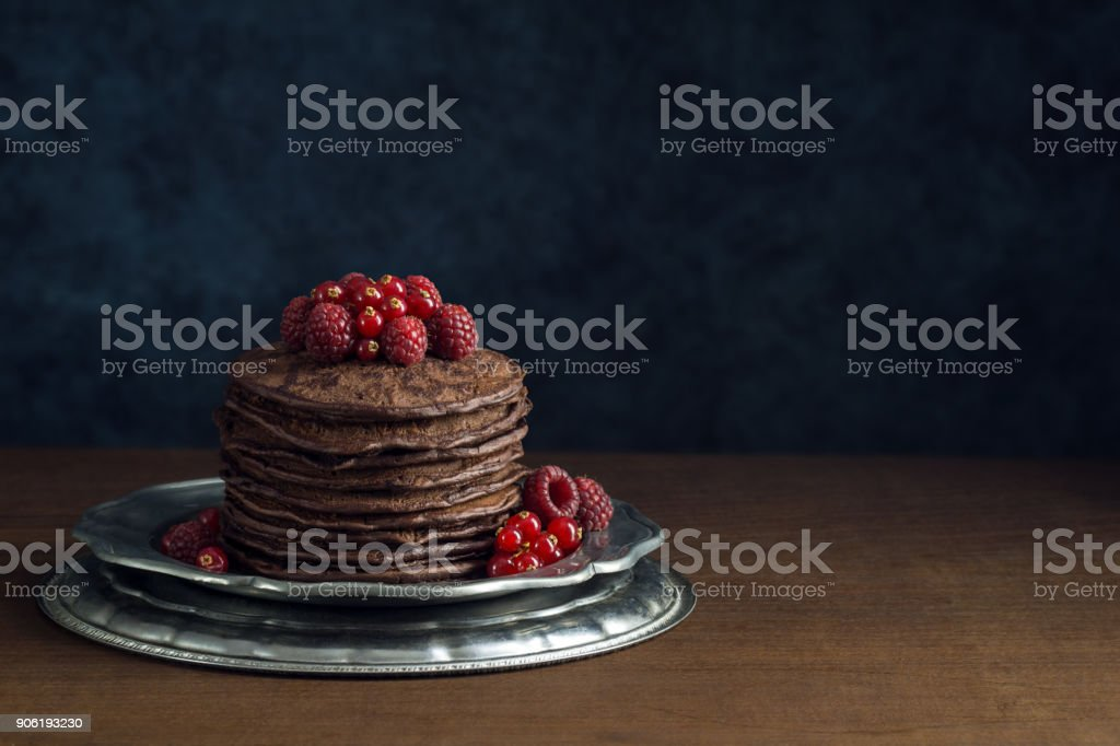 Stack of Dark Chocolate Pancakes Topped with Raspberries and Red Currants stock photo