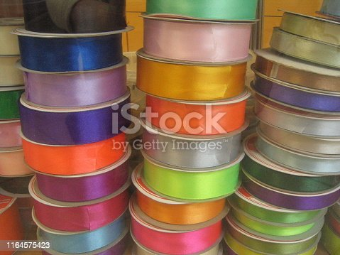 stack of decorative trim. bright ribbons in bobbins