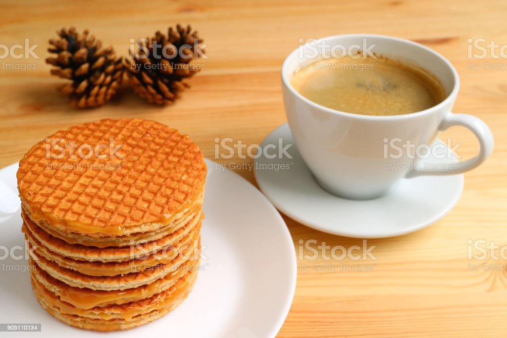 Stack of delectable Stroopwafel served on white plate and a cup of hot coffee on wooden table, with blurred pine cones in background stock photo