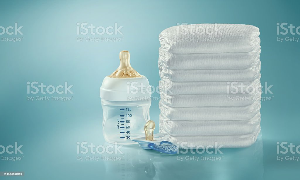 Stack of diapers. Baby bottle and pacifier. Studio Shot. Isolated stock photo