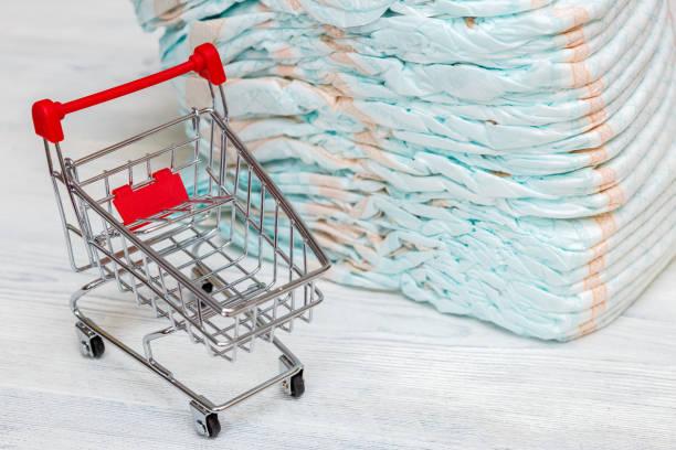 stapel von windeln oder windeln und mini-einkaufswagen, konzept - geld schön verpacken stock-fotos und bilder