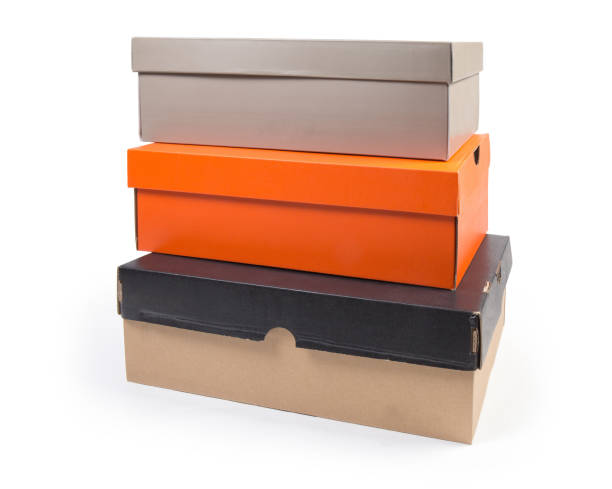 Stack of different closed cardboard shoe boxes on white background stock photo