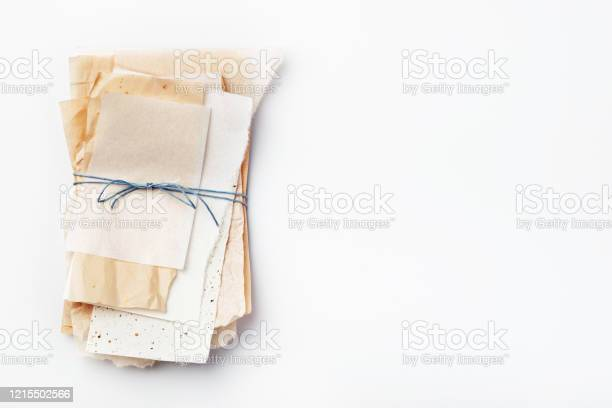 Photo of Stack of different pieces of paper tied with blue thread