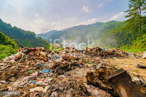 Stack of different types of large garbage dump, plastic bags, and trash burning near paddy rice terraces, agricultural fields of Mu Cang Chai, mountain in Vietnam in environmental pollution concept.