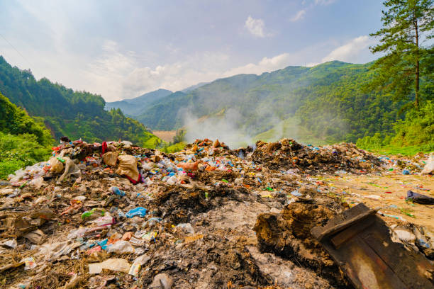 Stack of different types of large garbage dump, plastic bags, and trash burning near paddy rice terraces, agricultural fields of Mu Cang Chai, mountain in Vietnam in environmental pollution concept. stock photo