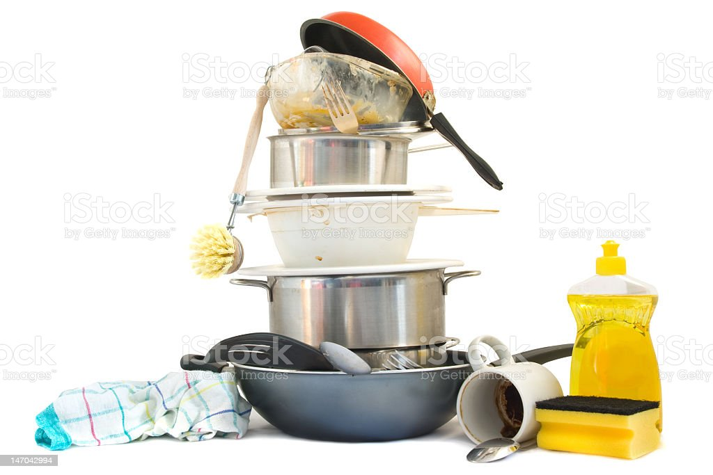 A stack of dirty dishes, pots, and pans by soap and rags stock photo