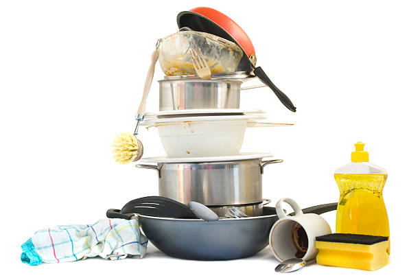 A stack of dirty dishes, pots, and pans by soap and rags foto