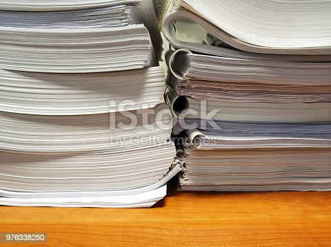 istock Stack of documents on desk 976338250