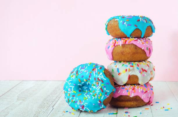 stack of donuts on a soft pink background - bombolone foto e immagini stock