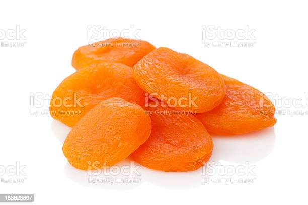 A Stack Of Dried Apricots Against A White Background Stockfoto en meer beelden van Abrikoos